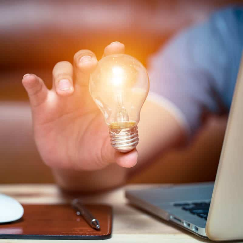 Man at laptop holding lightbulb