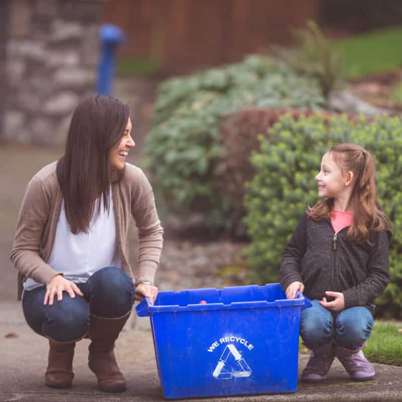 Woman and girl with recycling bin